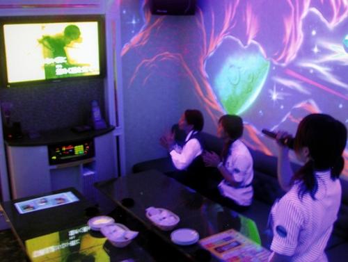 Друзья отлично проводят время в караоке-кабинке